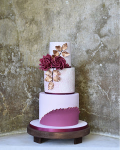 Rustic olive wooden cake stand round dark showcasing beautiful 3 tier cake with flowers and gold leaf