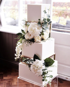 Gold square cake spacer supporting white wedding cake with stunning floral arrangements