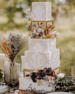 Gold rectangle cake spacers supporting stunning white and gold wedding cake with dried flower arrangements