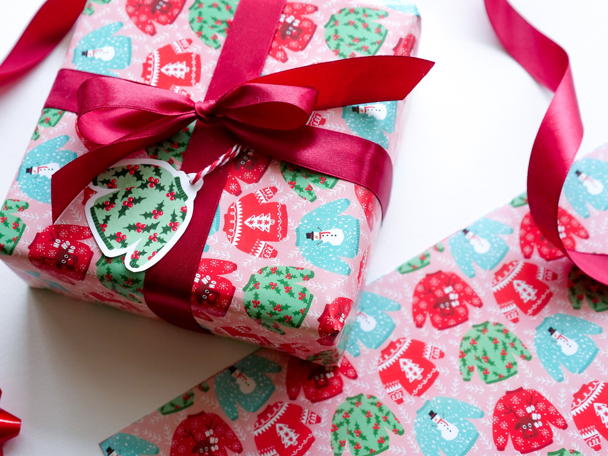 Christmas Jumper Wrapping paper with gift tag in pinks and greens HUTCH London