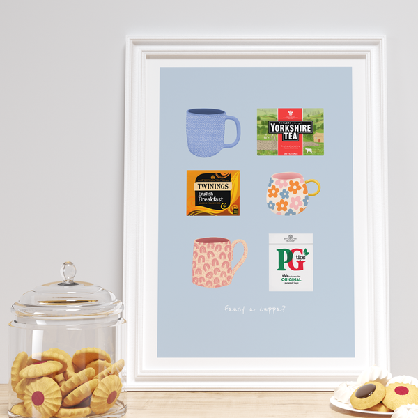 Digitally illustrated tea print with blue background featuring Yorkshire tea, twinings tea and pg tips alongside. cute mugs. Quote at the bottom saying 'fancy a cuppa?' photographed in white frame amongst cookies