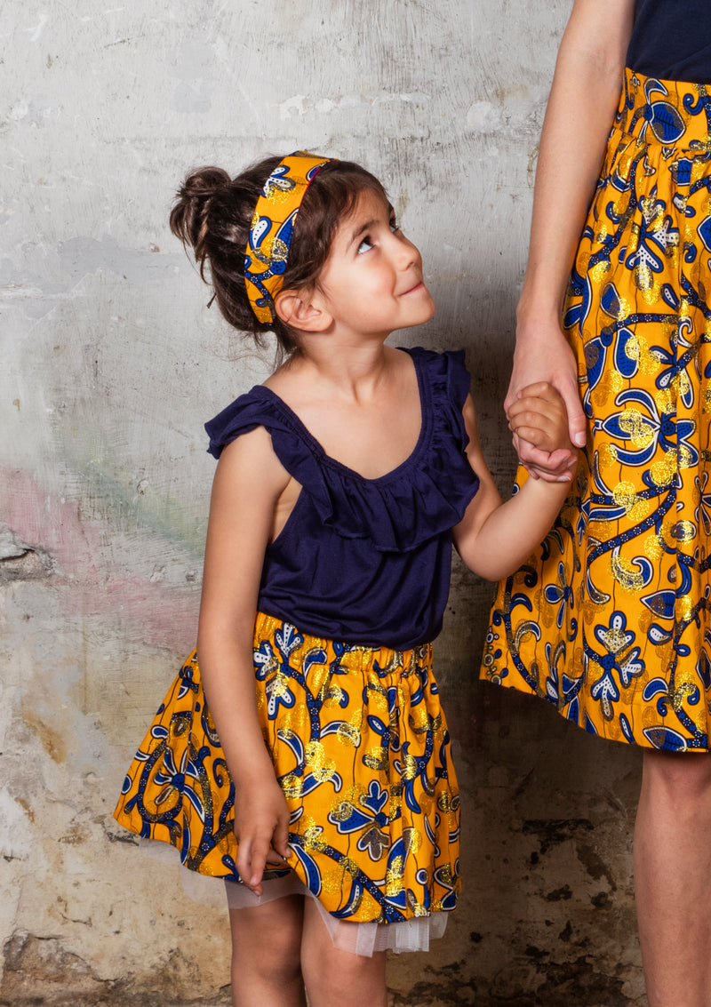 Cora & Lea - Niña- falda Twist and Shout. African Wax-Print, Estampado amarillo, azul y dorado.