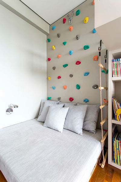 Climbing wall over a bed for kids to climb