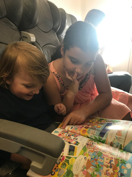 toddler on plane with activity book travelling with kids