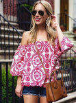Blonde Woman wearing sunglasses with handbag wearing red and white boho pattern off shoulder top