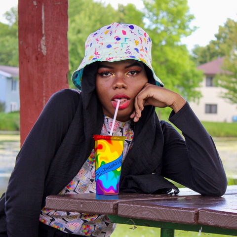 Hawwaa, designer of because, in. bucket hat sipping from a rainbow cup
