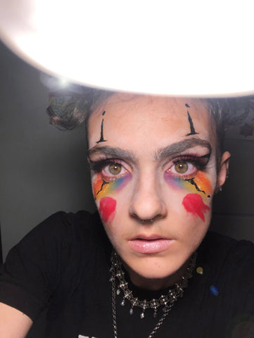 Madeline Dintino, a queer artist and creator of the Flower Punks Collective stares into the camera as a clown after a good cry, wearing Fluide products and other makeup.