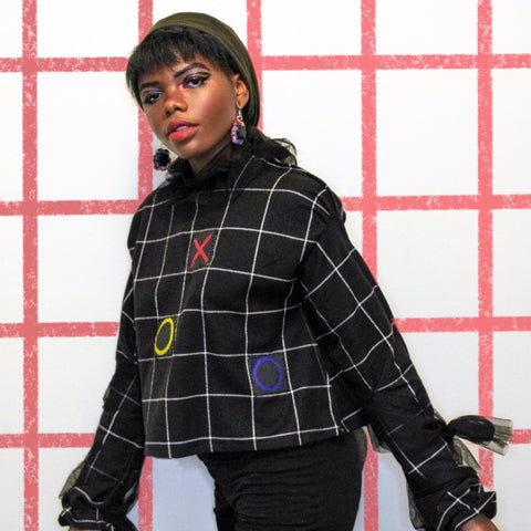 Hawwaa with grid background wearing a black and white tic tac toe patterned jacket