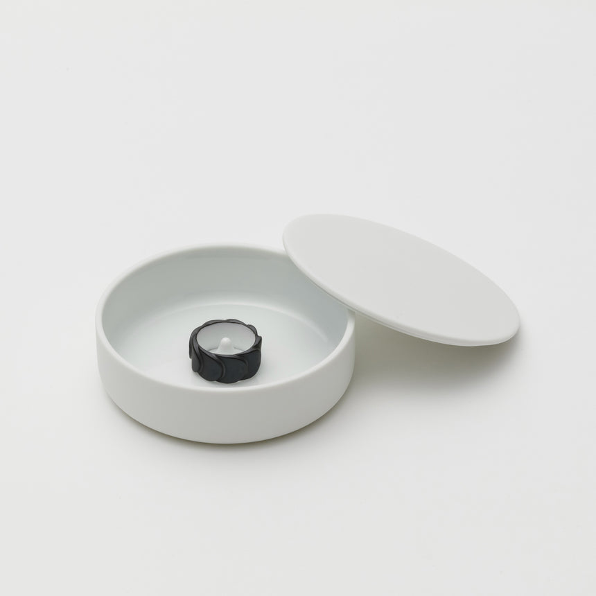 White porcelain jewelry holder designed by Saskia Diez for Arita 2016. Handmade in Japan. Glazed interior, matte exterior. Water drop detail in middle with thin walled lid leaning on side of base. Black ring inside.