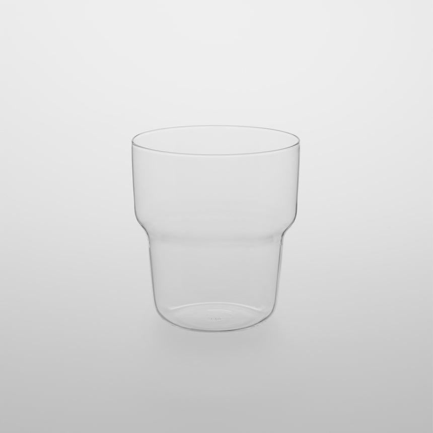 Small stackable curved glass tumbler cup. Designed by Naoto Fukasawa for TG Taiwan Glass. Clear borosilicate on grey background.