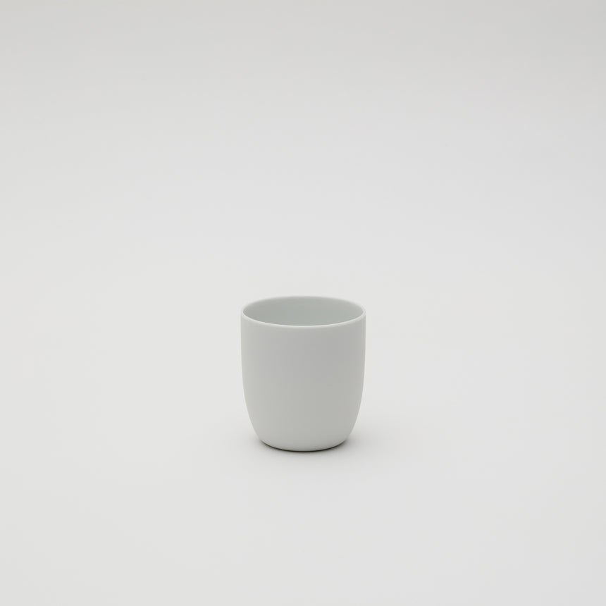 White porcelain cup designed by Leon Ransmeier, made in Arita, Japan. Soft lines, unglazed exterior. Contemporary ceramics.