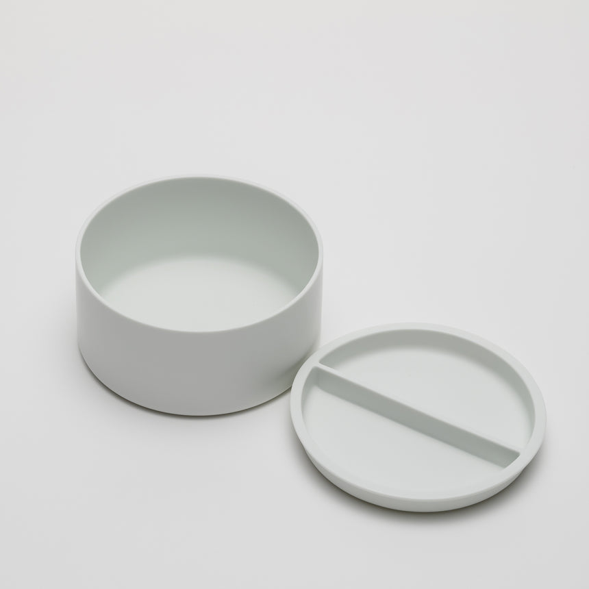 Wide, short porcelain container designed by Shigeki Fujishiro for Arita 2016. Handmade in Japan. Contemporary ceramic with fitted lid, unglazed exterior, matte finish. Top removed and set next to container.