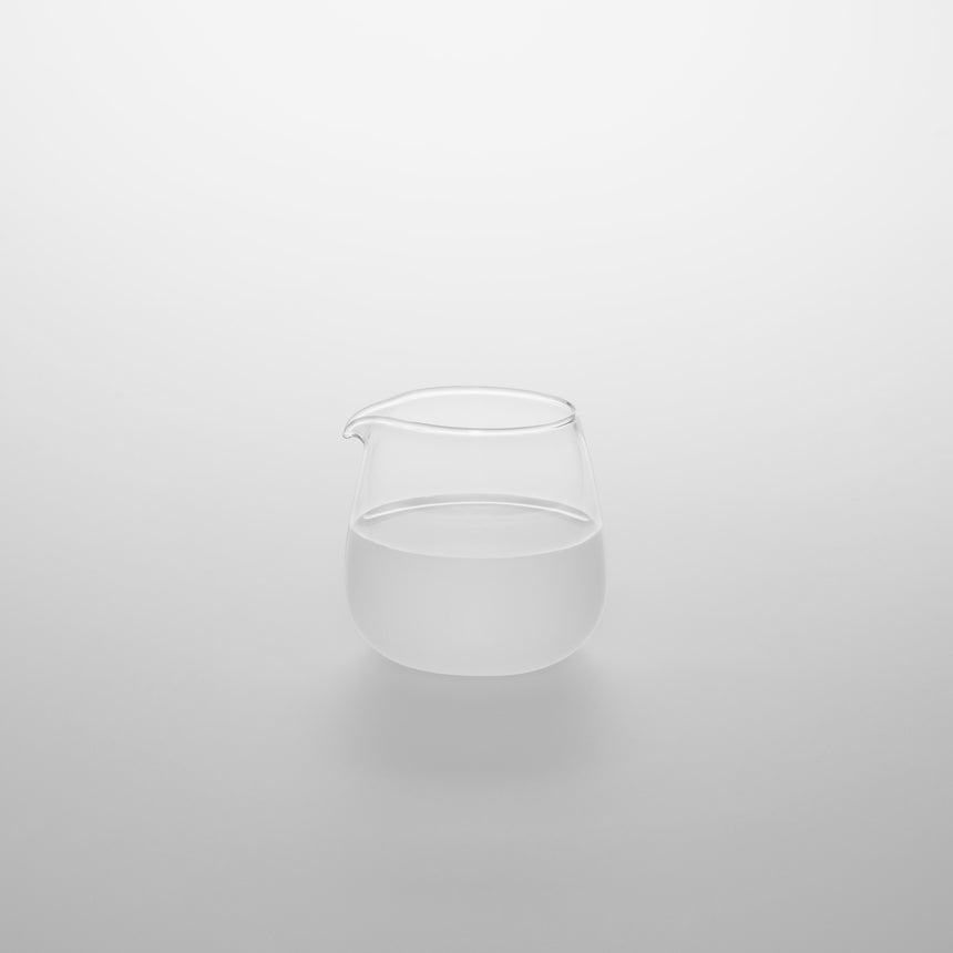 Small clear glass milk creamer with spout. Designed by Naoto Fukasawa for TG Taiwan Glass. Clear borosilicate on grey background.