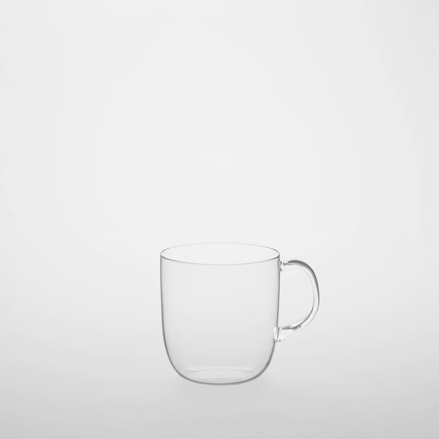 Glass pitcher with fitted cup Designed by Naoto Fukasawa for TG Taiwan Glass. Clear borosilicate on grey background. Cup is on top of pitcher.