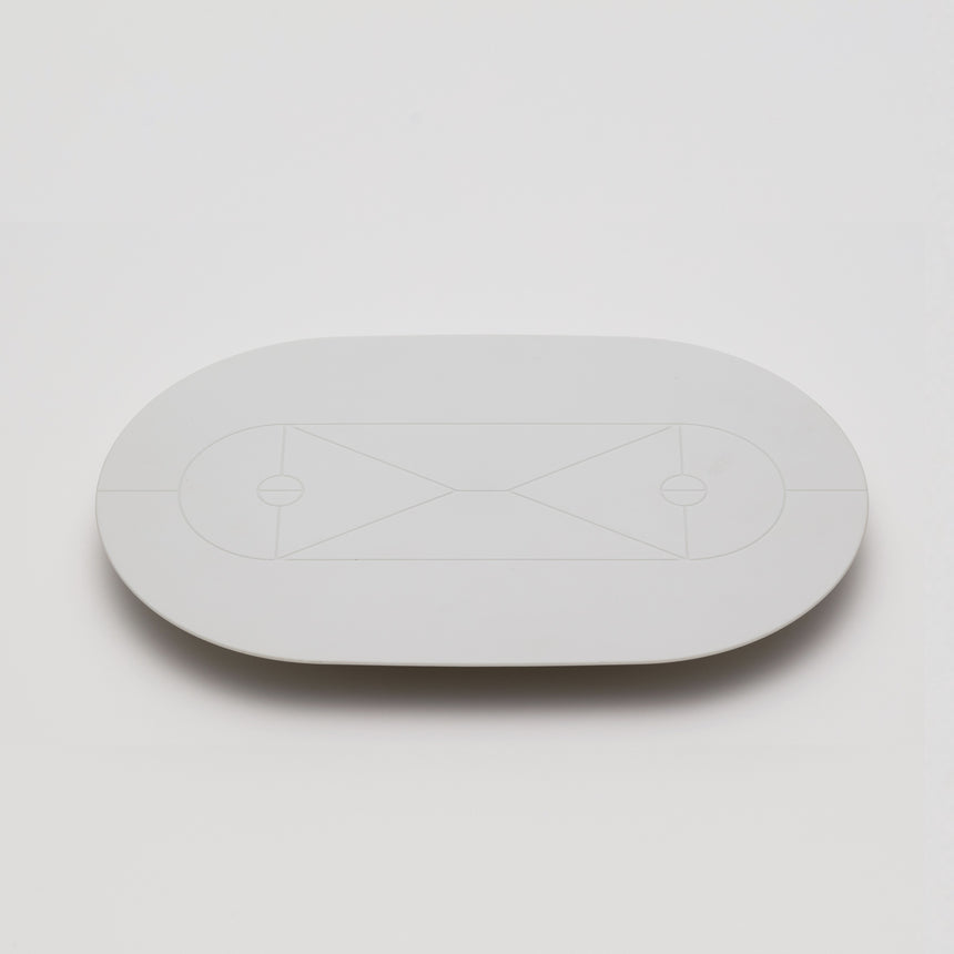 White matte serving tray designed by Christian Haas for Arita 2016. Handmade in Japan. Elongated circular serving tray, elevated by triangular feet with geometric court-style patter on surface.