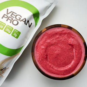 Pink red coloured smoothie with Vegan Pro pouch on the side