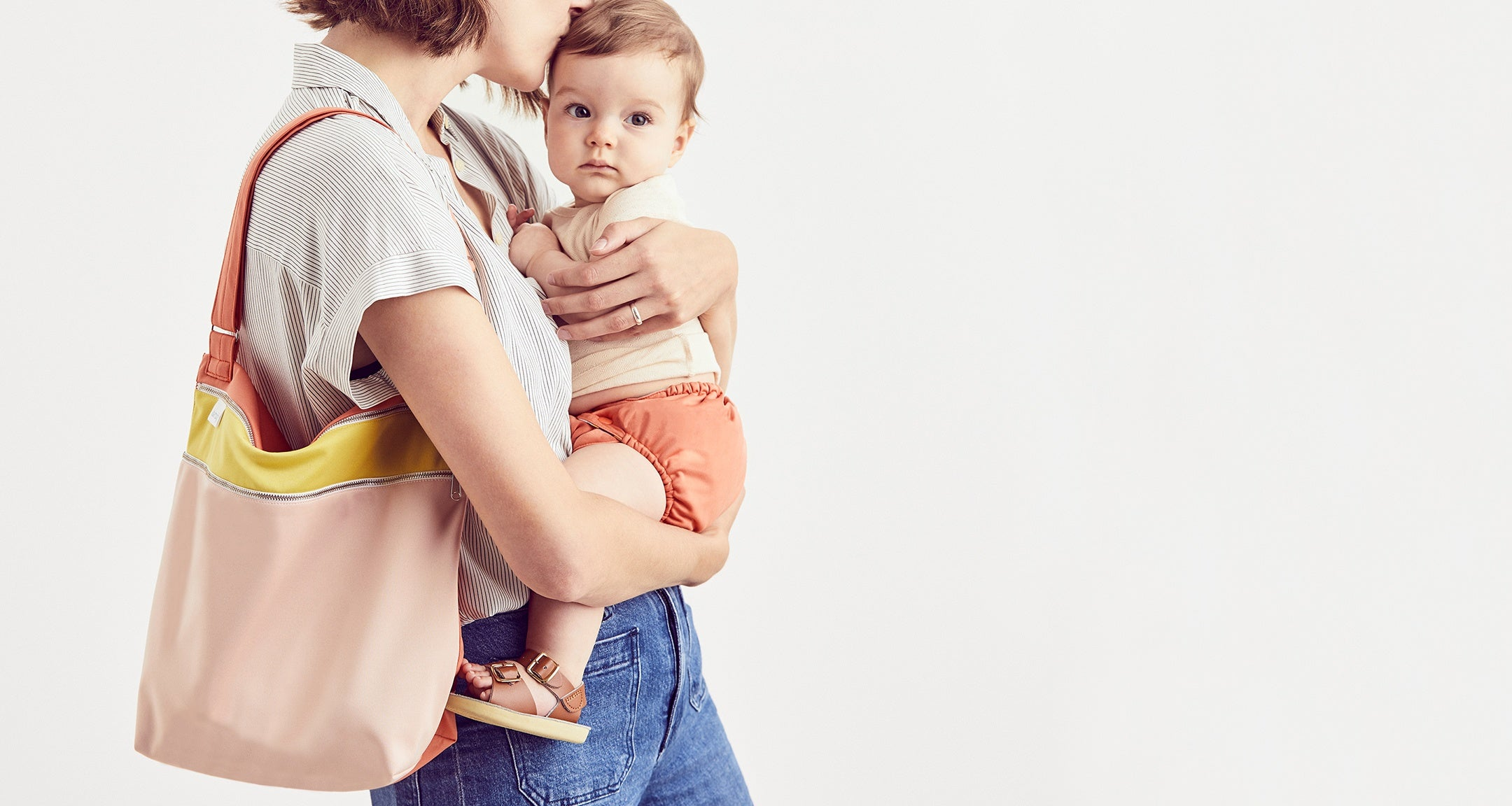 A mom and her baby rocking an Esembly day bag in blush