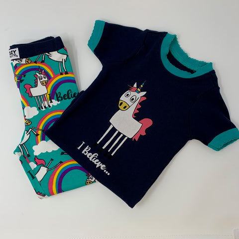 "Children's Unicorn I Believe Pajama Set Navy Short Sleeve Top with Turquoise Collar and Sleeve Details, White Cartoon Unicorn with Pink Mane and Tail and Multi-Color Horn in Center ""I Believe..."" In Script Under, Turquoise with Navy Band Bottoms, Unicorn, Rainbows, Clouds, and ""I Believe..."" Repeated in Overlapping Pattern"