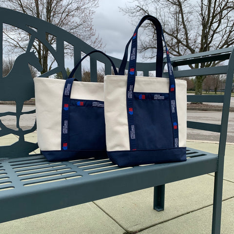 Two American Saddlebred Horse Association Totes Small Natural Color with Navy Bottom Handles White Text and Blue and Red Logo Sitting on Saddlebred Bench