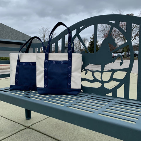 American Saddlebred Museum Totes Small Natural Canvas with Navy Bottom Middle and Handles White American Saddlebred Museum Logos on Handles Sitting on Saddlebred Bench Outside Museum