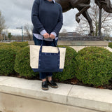American Saddlebred Museum Tote Large Natural Canvas with Navy Bottom Middle and Handles White American Saddlebred Museum Logos on Handles Held in Two Hand by Woman Standing on Short Wall By Shrubbery and Horse Statue