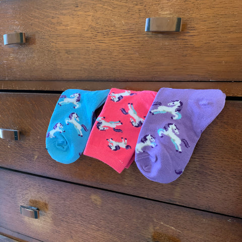 Children's Youth Socks in Blue Pink and Purple Hanging Over Dresser Drawer with White and Purple Dancing Horses