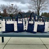 4 American Saddlebred Museum and American Saddlebred Horse Association Totes Small and Large Natural Canvas with Navy Bottom Middle and Handles White American Saddlebred Museum Logos and White Red and Blue ASHA Logos on Handles Sitting on Saddlebred Bench