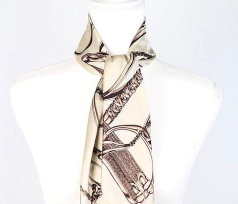 Beige English Horse Silk Scarf with Brown Equestrian Print of Stirrups, Bits, and Leather Tied Around Neck of Form