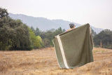 Whup Trot Travel Blanket Olive Green with Light Brown and Cream Stripes on Ends Woman Standing in Field with Blanket Spread Over Shoulders