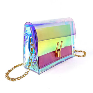 Clear holographic crossbody bag with gold chain and pink panel.