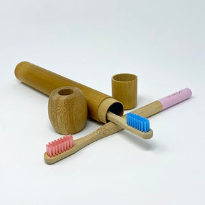 Two bamboo toothbrushes with pink handles and pink bristles, resting on a bamboo toothbrush case and next to a bamboo toothbrush stand.