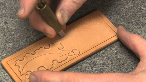 The artisan is carving image on the vegetable tanned leather