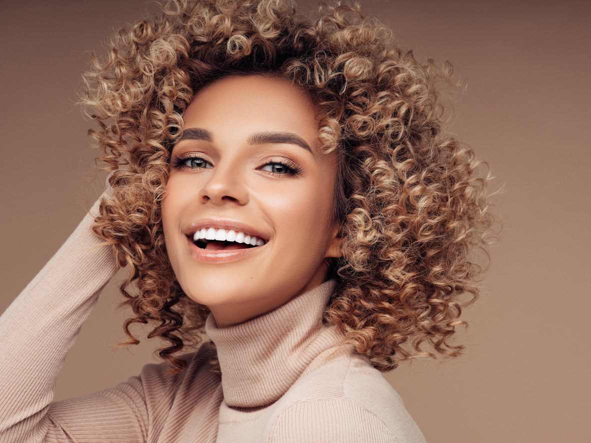 Biracial woman with blonde, coily hair smiling at the camera while wearing a turtleneck