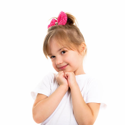 child with ponytail and pink bow