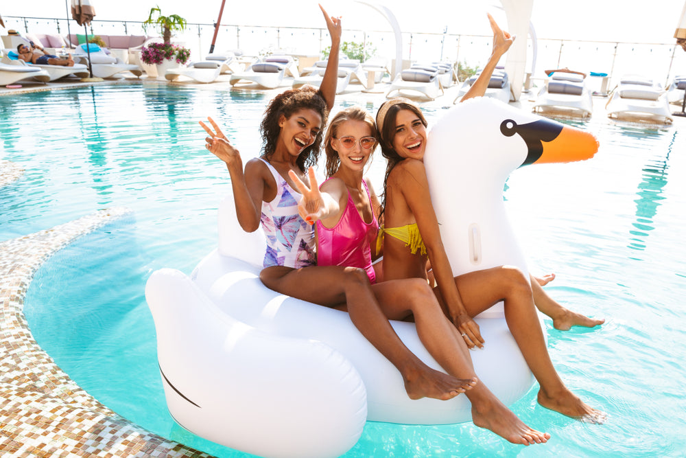 Summer Hair | 6 Ways to Protect Hair from Chlorine Damage | Three Cheerful Young Women Swimming Poolside