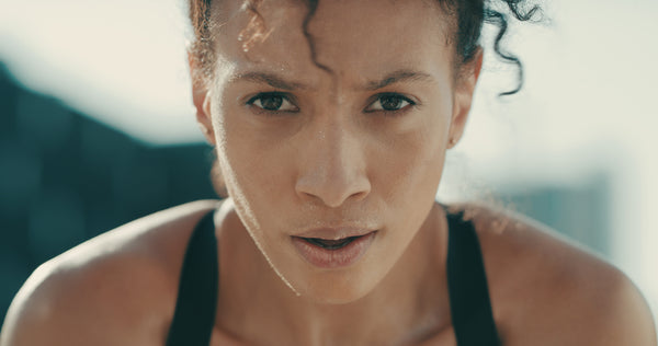 Beautiful woman with dark curly hair seating during a workout