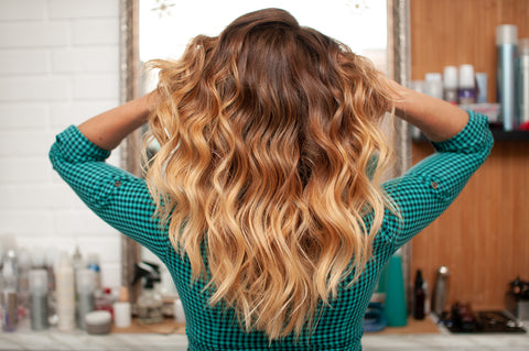 Woman in green facing a mirror with different hair care products while holding her brown ombre curly hair
