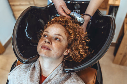 Red-haired woman having her hair washed by a hair stylist in a salon.