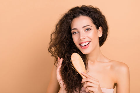 Close-up portrait of curly-haired young woman smiling and combing her hair with a hair brush.
