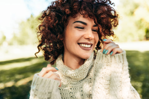 Close-up portrait of curly-haired young woman smiling and touching her hair.