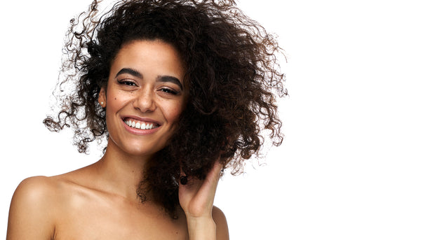person with curly hair smiling
