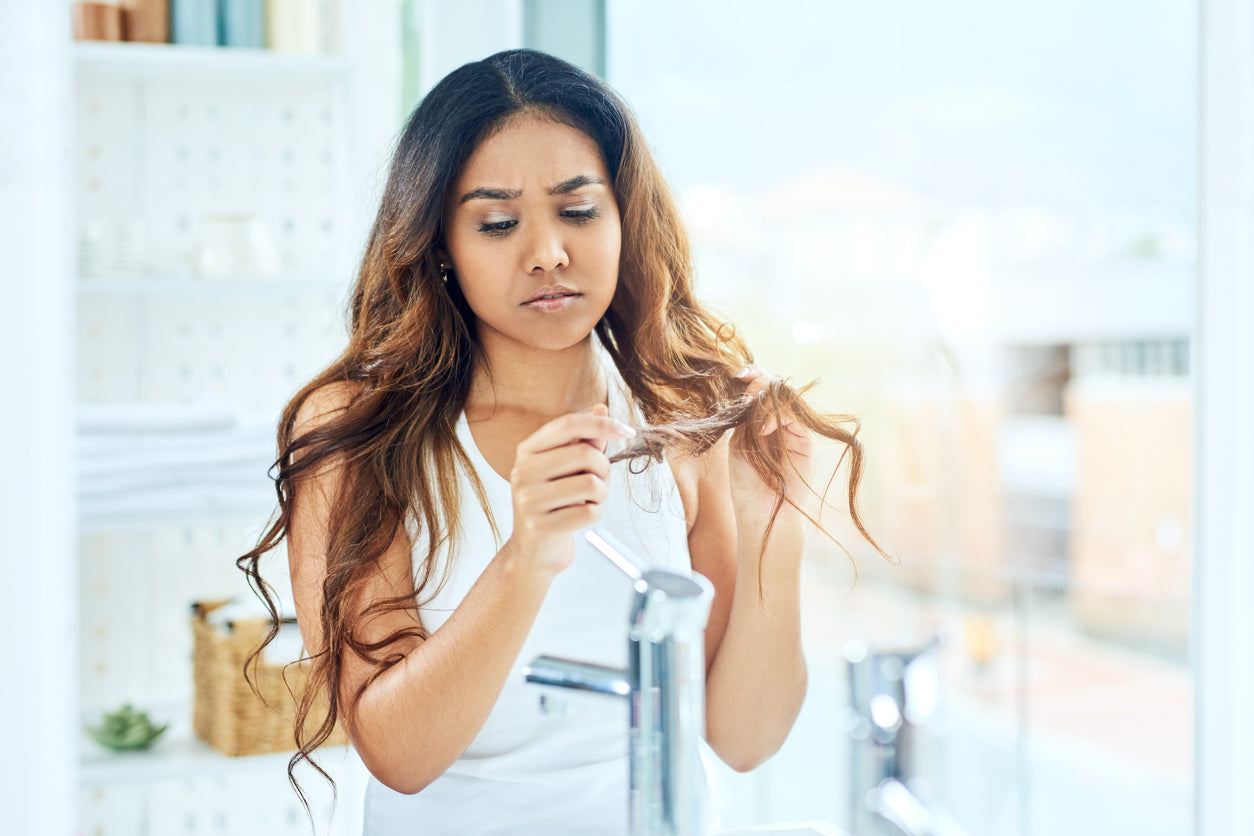 frustrated woman looking at her dry hair's ends