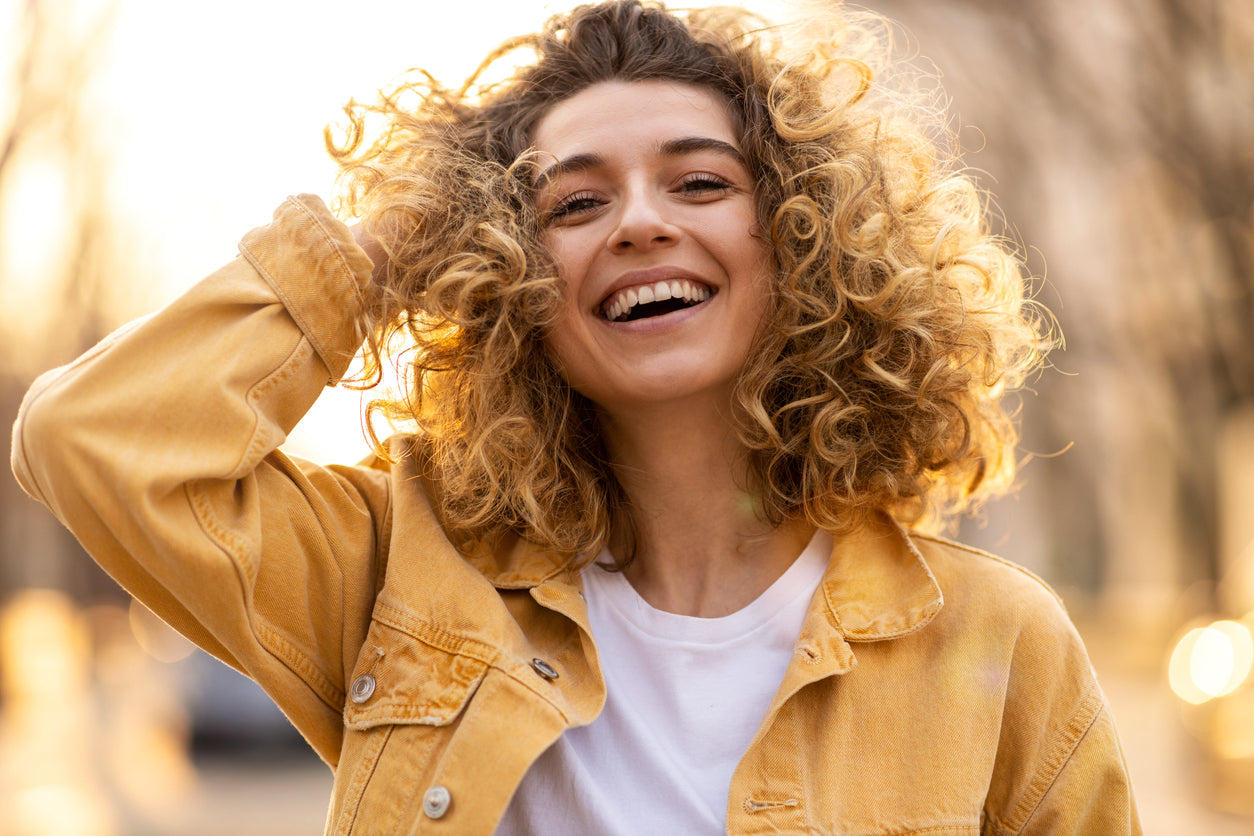 caucasian woman with light curly hair smiling at the camera