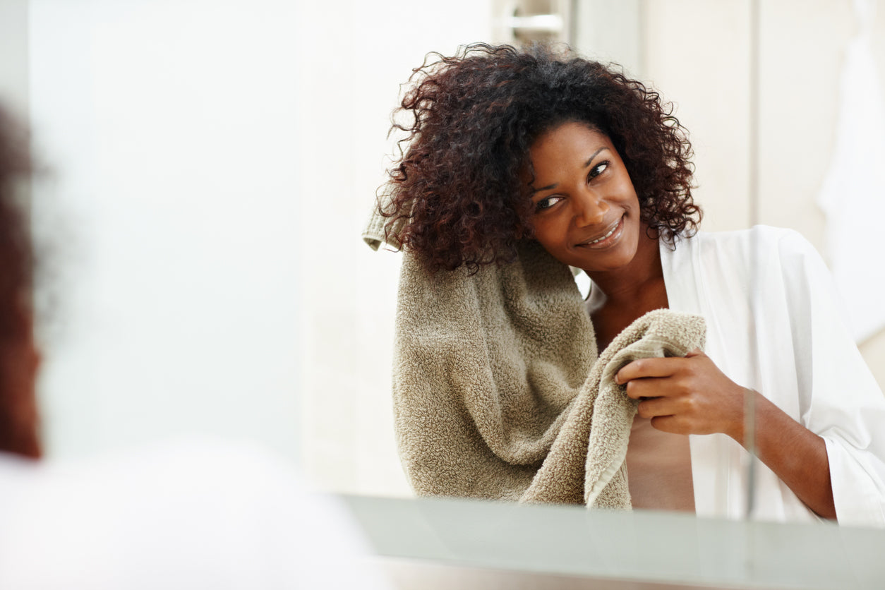 black woman drying her hair with a towel right after coming out of the shower