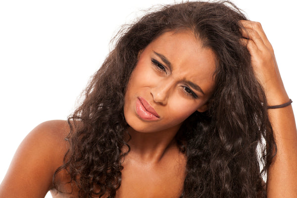 A young frustrated woman with long curly hair scratching on her scalp.