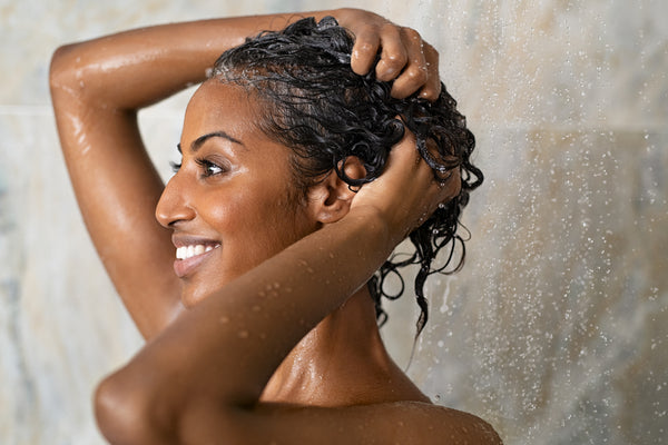 Woman washing her long curly hair with a clarifying shampoo in the shower.
