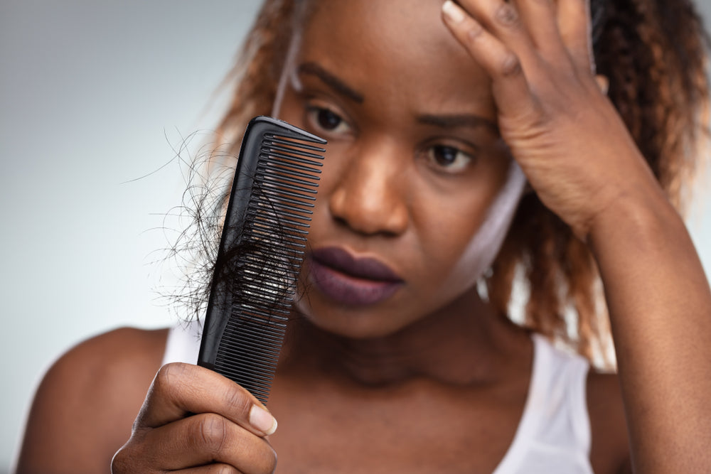 Woman looking it comb with hair loss