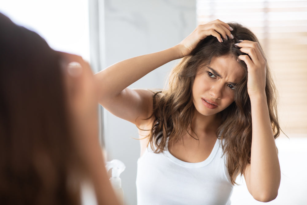 Healthy Scalp | Woman looking at scalp in mirror