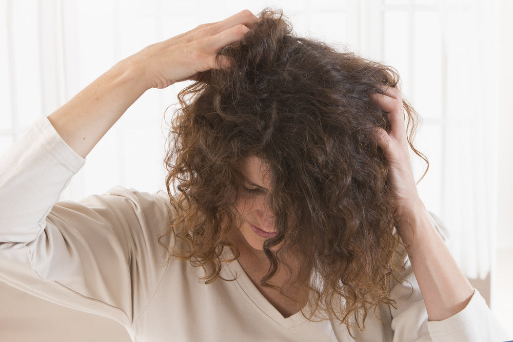 Woman with curly hair massaging product into scalp