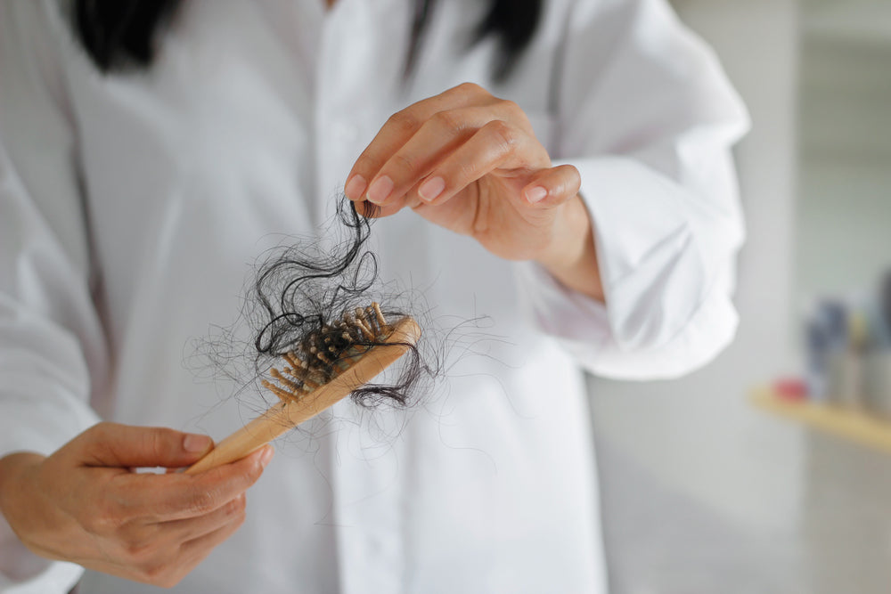 Woman pulling hair from her hairbrush